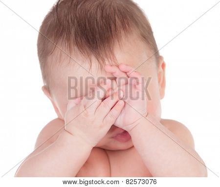 Sleepy baby covering the face with his hands isolated on a white background