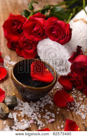 Red rose with petals in bowl with pile of salt ,stones ,towel on old wooden board