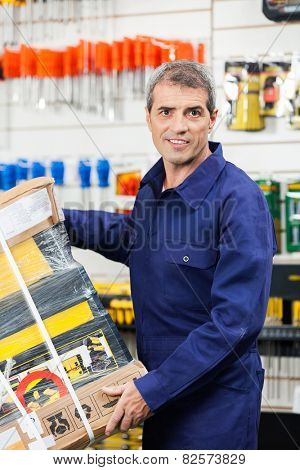 Portrait of mature worker carrying tool package in hardware shop
