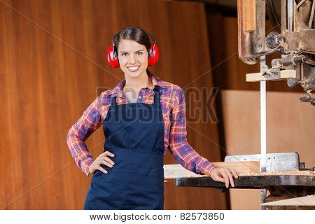Portrait of confident female carpenter with hand on hip standing by bandsaw in workshop