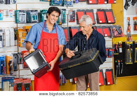Portrait of smiling salesman with senior man choosing toolbox in hardware store