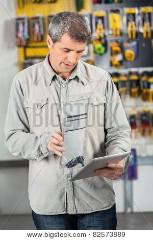 Mature male customer scanning product through digital tablet in hardware store