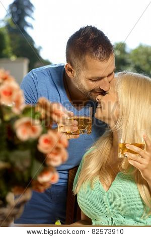 Portrait of romantic young couple kissing with drinks in hand, outdoors. Attractive, busty blonde woman with cleavage.
