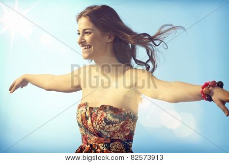 Happy young woman flying on summer sky, enjoying freedom arms wide open.