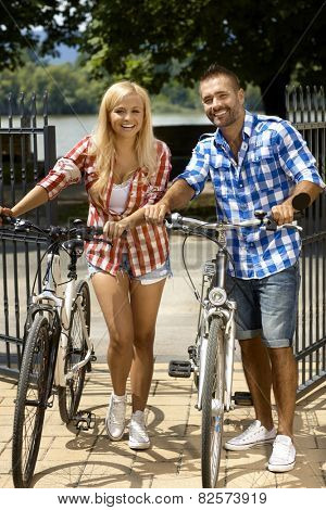 Happy sporty casual couple going for bicycle ride. Attractive blonde woman and handsome stubbly man. Smiling, sport activity, summer. Looking at camera, full size.