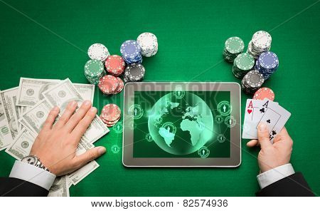 casino, online gambling, technology and people concept - close up of poker player holding playing cards, chips and earth projection with users icons on tablet pc computer screen at green casino table