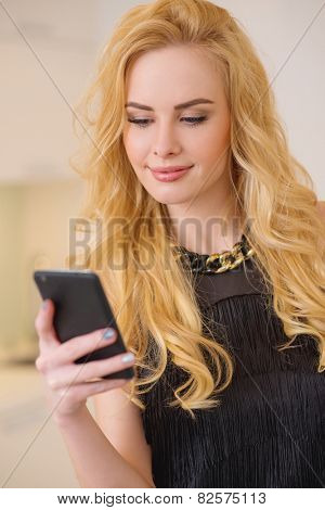 Close up Attractive Young Blond Woman in Black Clothing  Busy Messaging Using her Mobile Phone.