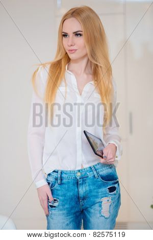 Close up Stylish Blond Woman Wearing Trendy Long Sleeve Shirt and Tattered Jeans with Tablet Device on her Hand.