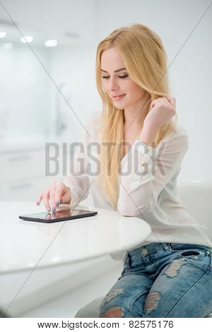 Close up Pretty Young Woman with long Blond Hair Sitting at the White Table  with Tablet Computer