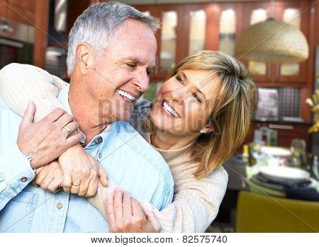 Happy senior loving couple over house background