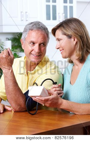 Senior woman and man measuring blood pressure.