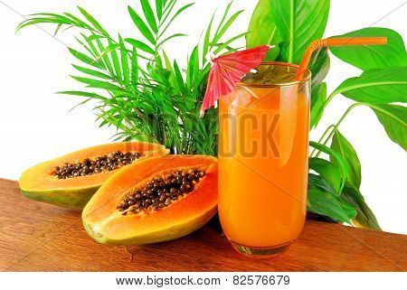 papaya fruit and glass of juice and exotic leaves