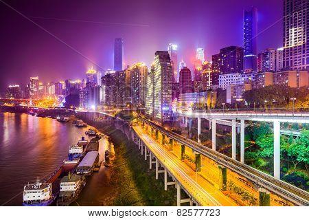 Chongqing, China riverside cityscape at night.