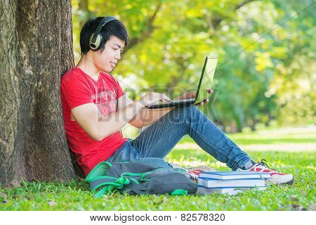 Education, Technology And Internet Concept - Smiling Teenager Using Laptop Computer With Earphone