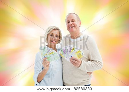 Happy mature couple smiling at camera showing money against girly pink and yellow pattern