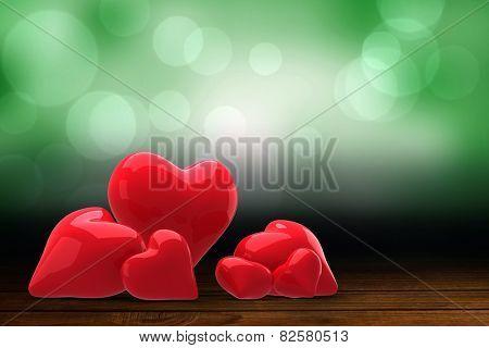 Love hearts against shimmering light design over boards
