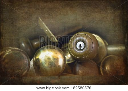 Old brass door knobs discarded on a shelf in a workshop. Textured and filtered to look like an old faded photograph.