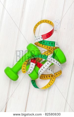 Dumbells and tape measure over wooden background. View from above