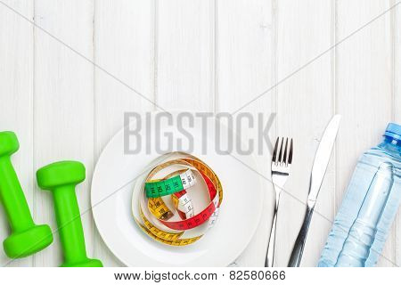 Dumbells and healthy food over wooden background. View from above with copy space