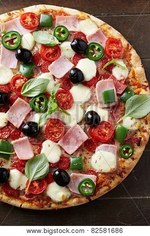 Pizza with ham, pepperoni, peppers and mozzarella