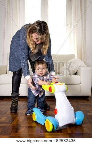 Young Mother And Little One Year Old Son Walking With Baby Walker Taking His First Brave Steps