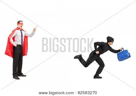 Full length portrait of a superhero chasing a burglar isolated on white background