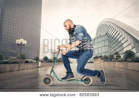 Young man riding a push scooter