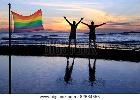 Silhouette of two men at sunset with a gay pride flag in the foreground.
