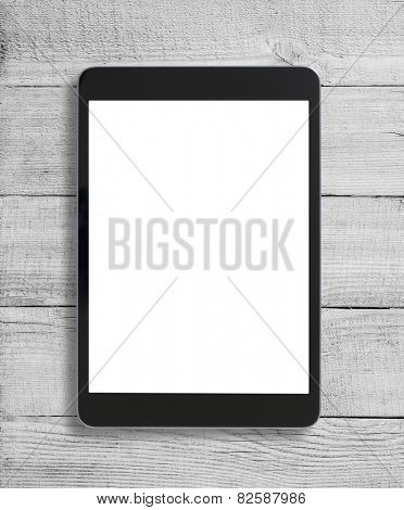 Black tablet pc similar to ipad on wood table background