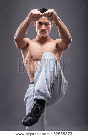 Young asian man workout over grey background karate kick