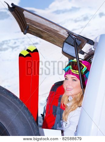Woman comes on ski resort, sitting on the car with all sports equipment, enjoying winter holidays, active vacation concept