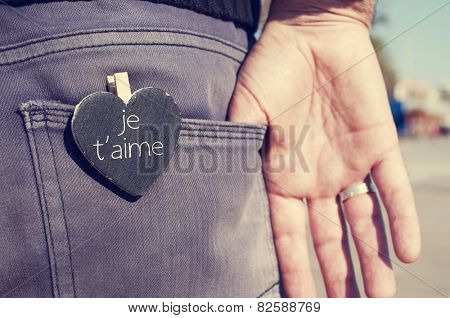 a heart-shaped chalkboard with the text je t aime, I love you written in french, in the back pocket of the trousers of a young man