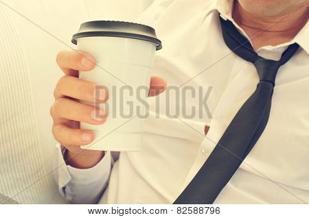 a young man with his necktie loosened drinking coffee in a paper cup