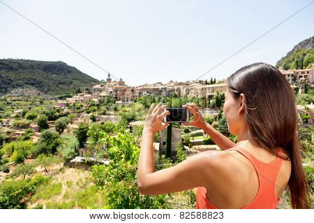 Tourist taking picture of Deia Village in Mallorca. Travel woman hiker using smartphone app to take a landscape photo of the Unesco World Heritage site on Majorca, Balearic Islands, Spain.