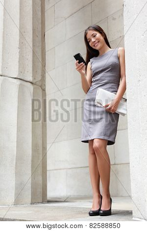Business woman lawyer using apps on smartphone outside to read news or text sms. Successful young multiracial Caucasian / Asian Chinese professional woman standing in suit dress holding newspapers.