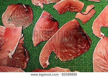 Raw tuna meat fillets or slices display in Tsukiji fish market, Tokyo, Japan. Famous touristic attraction selling raw seafood in the morning.