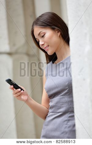 Urban smart casual businesswoman using app on smartphone. Young Asian Caucasian adult woman touching smart phone using 3g 4g app to read online or sms texting.