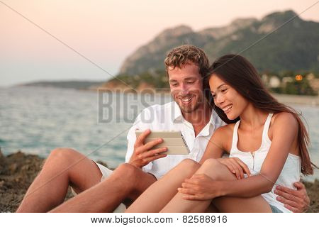 Romantic couple relaxing on beach using tablet computer at sunset. Young multiracial couple using apps on digital tablet taking pictures or reading e book looking at touch screen together.