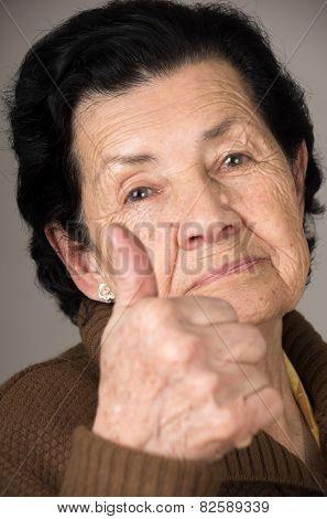 closeup portrait of grandma old woman holding thumb up