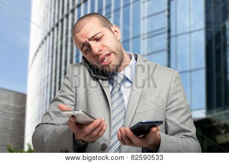 Portrait of a busy businessman using three phones at once
