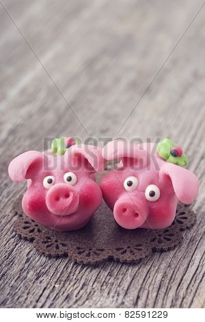Marzipan pigs on wooden background