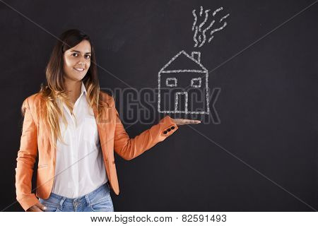 Happy woman showing a house drawing in the chalkboard