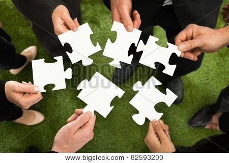 Businesspeople Hands With Jigsaw Puzzle
