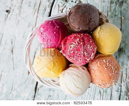 Ice cream scoops on wooden table, close-up.