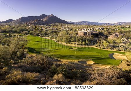 Wide angle high view point of desert golf course landscape community with mountains in background.