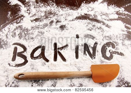 Word baking written in white flour on a wooden table