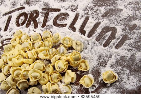 Fresh, raw tortellini with flour on wooden table