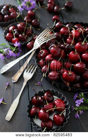 Fresh summer cherries and flowers in aluminum plates