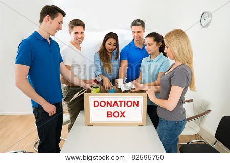 People Putting Cans In Donation Box