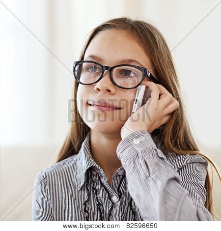 Portrait of 8 years old school girl wearing glasses calling by mobile phone